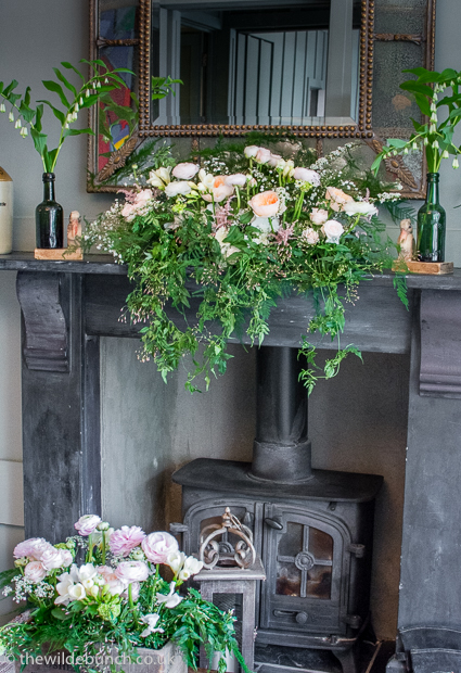 Peach wedding flowers on mantlepiece